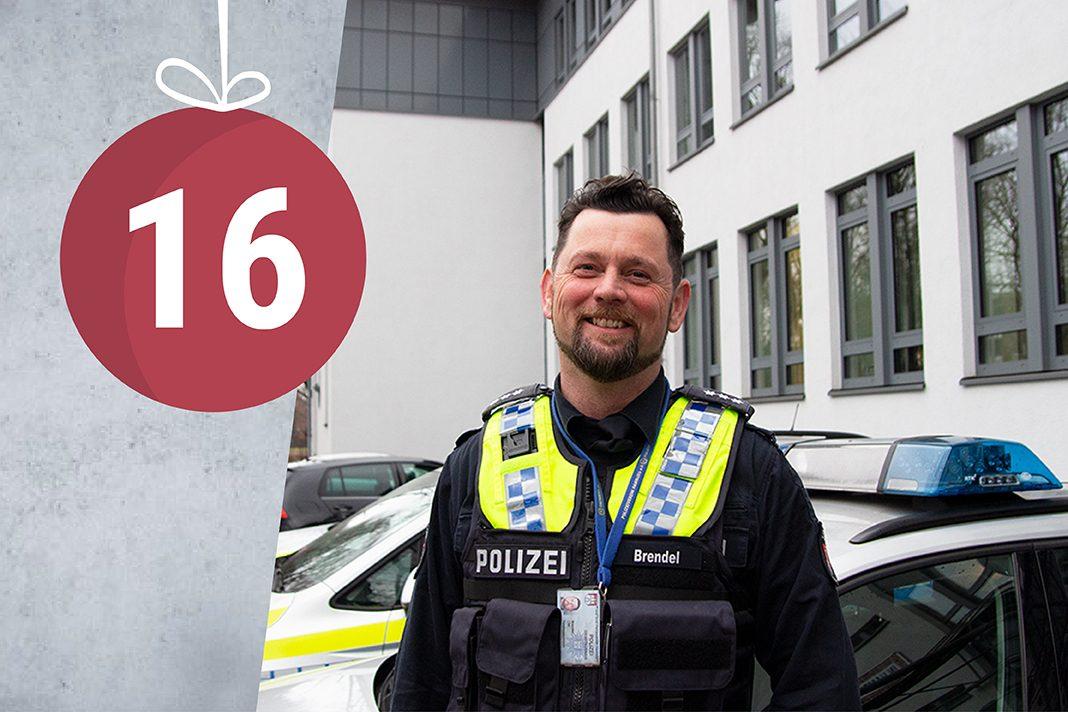 Polizist Olaf Brendel steht vor der Wache in Wilhelmsburg und lächelt.