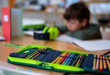 Im Vordergrund ist ein Etui zu sehen, im Hintergrund ein Schulkind. Foto: Sven Hopppe/dpa