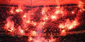Der Auswärtsblock im Volksparkstadion ist rot erleuchtet. Fans von Dynamo Dresden haben dutzende Pyrofackeln gezündet. Foto: Christian Charisius/dpa