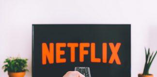 Eine Fernbedienung schaltet den Fernseher an, auf dem das Netflix-Emblem erscheint. Foto: Unsplash