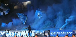 Der HSV-Auswärtsblock ist in blauen Rauch gehüllt. Foto: Andreas Gora/dpa