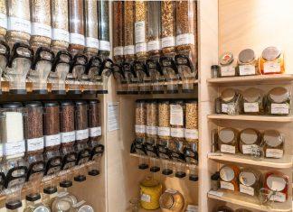 Unverpackt einkaufen: Cerelalienspender hängen in einem Ladengeschäft an der Wand und sind gefüllt mit Nüssen, Flocken und Schokostreuseln.