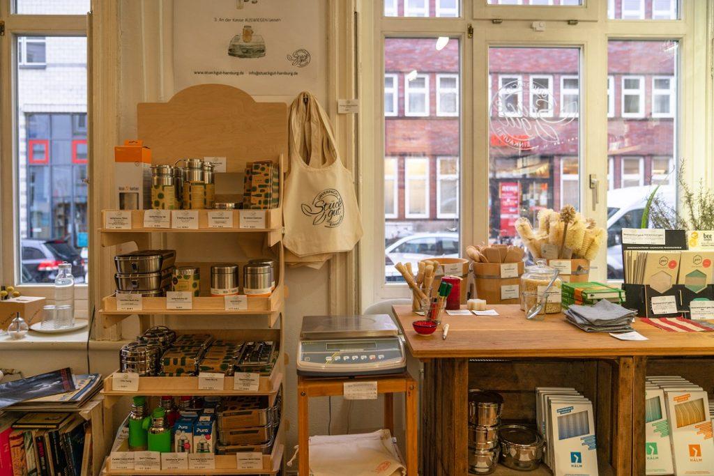 Regale mit Metallbehältern, Bienwachstüchern und einer Waage in einem Geschäft.