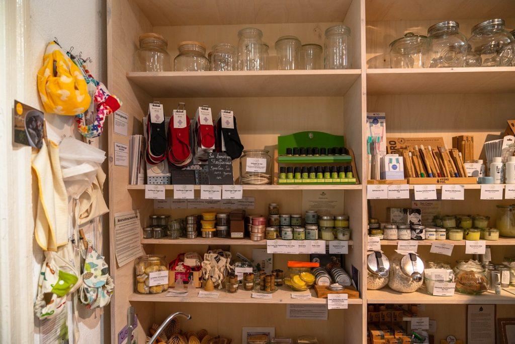 Regal mit unverpackten Seifen, Bambuszahnbürsten und Cremes in Döschen.