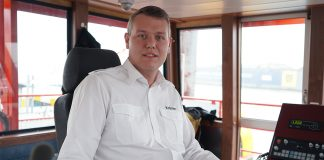 Alexander Krämer sits in the wheelhouse of a ferry in the port of Hamburg
