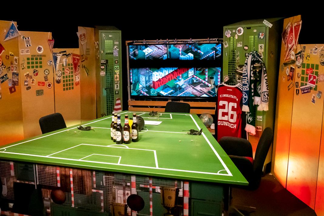 Ein Tisch, der wie ein Fußballfeld aussieht mit vier Stühlen darum.