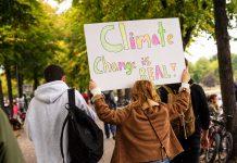 """Eine Frau die ein Plakat hoch hält. Darauf steht """"Climate Change is real"""""""