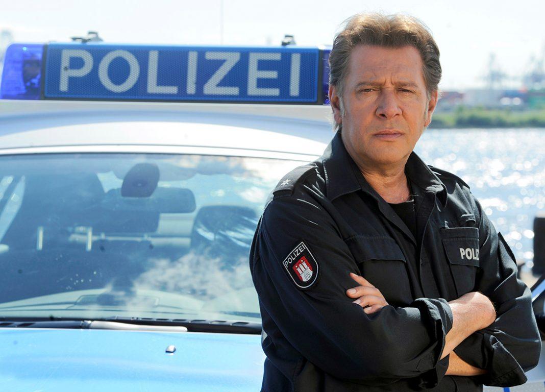 Jan Fedder steht vor einem Polizeiwagen in Hamburg.