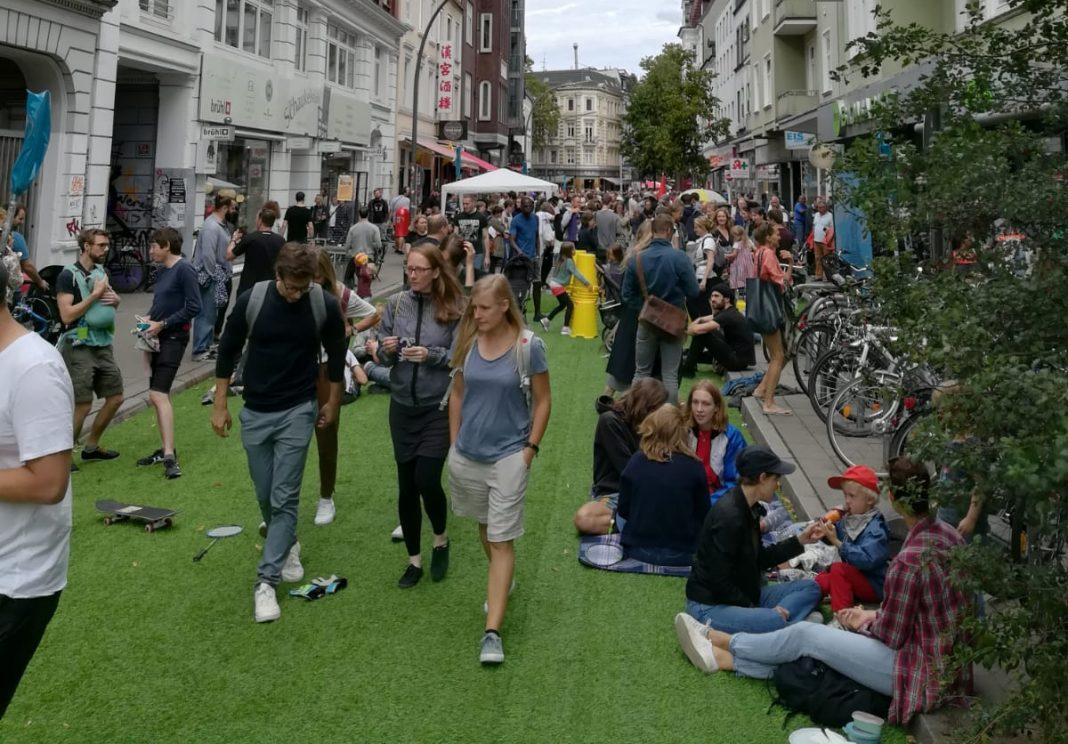 Die autofreie Straße in Ottensen mit Rollrasen auf dem Asphalt und Menschen auf der Straße