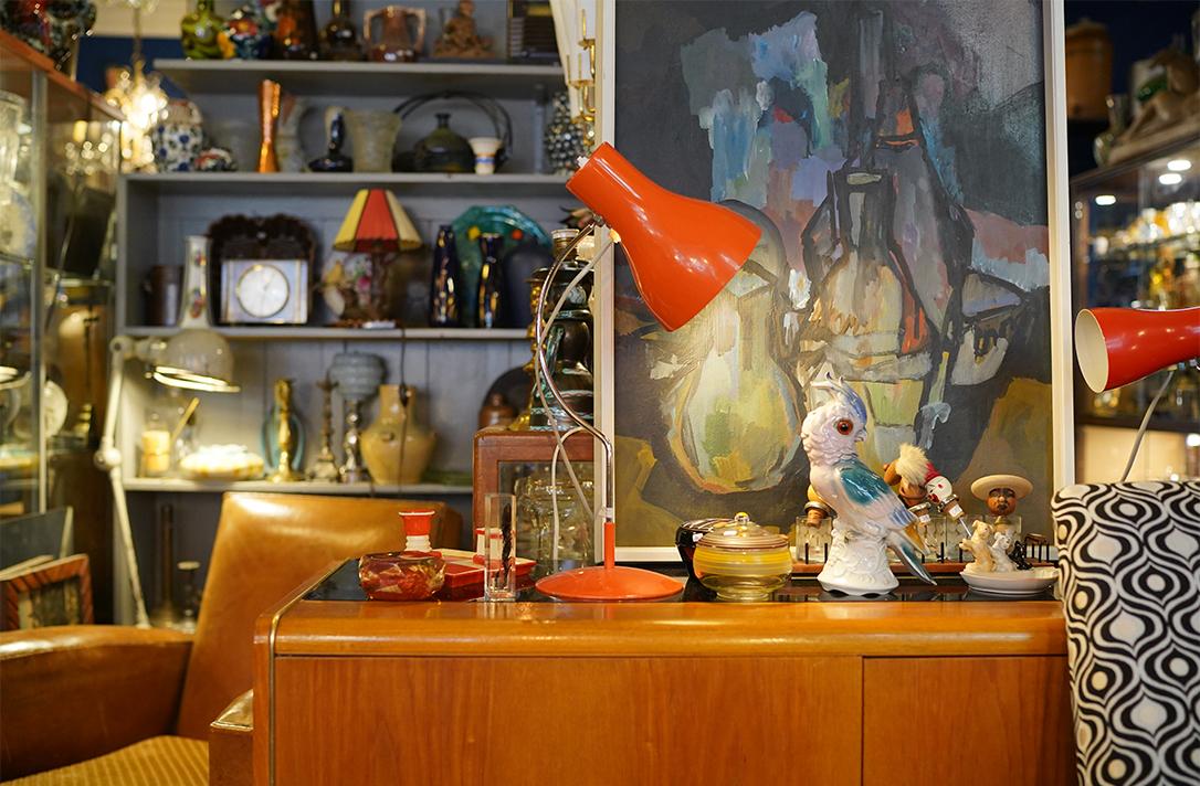 Eine alte rote Lampe steht auf einem Holzsideboard.