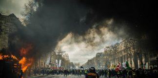 Diskussion um das Vermummungsverbot, Bild einer Demonstration: Vermummte Personen und eine brennende Mülltonne.