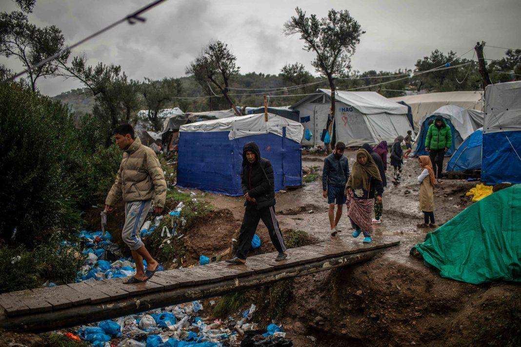 Migranten überqueren eine Holzbrücke in einem Zwischenlager neben dem Lager Moria auf der Insel Lesbos.