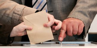Helfer hilft Wählern beim Stimmzettel