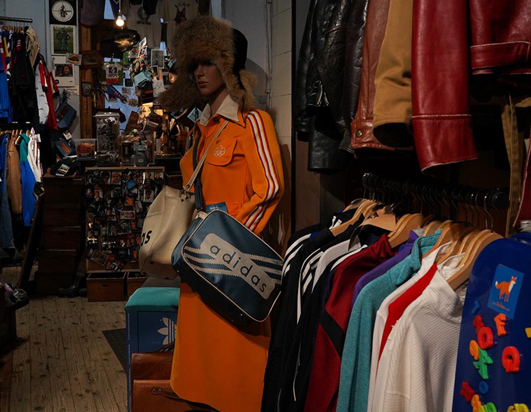 Eine Schuafensterpuppe trägt ein orangenes Stewardess Outfit.