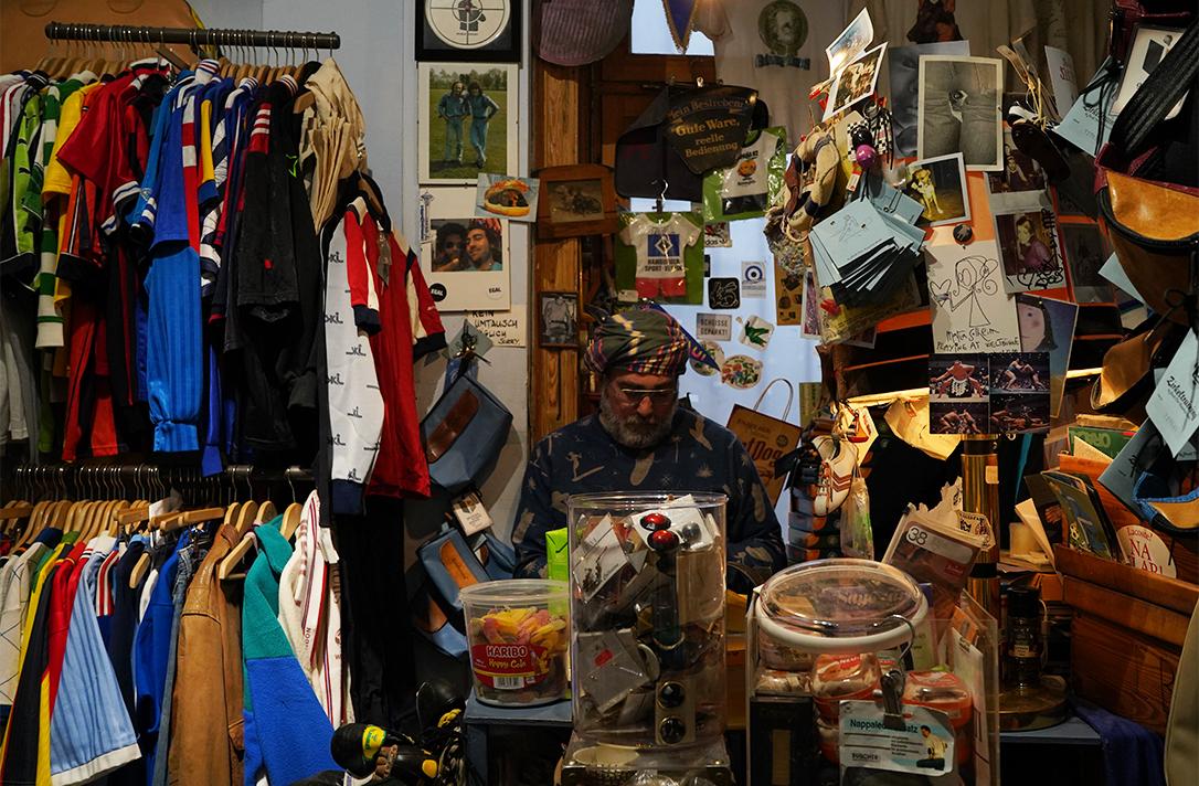 Mann sitzt hinter der Kasse und zwischen vielen Klamotten.