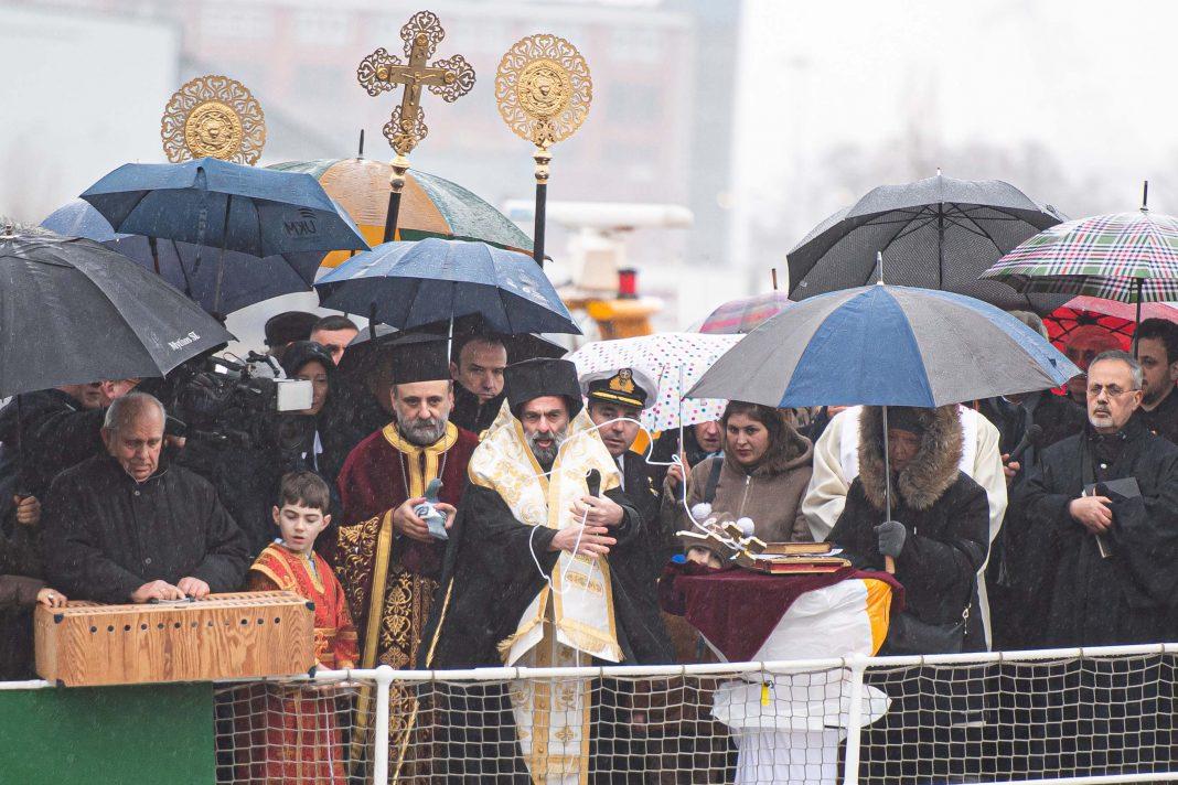 Grieschisch-orthodoxer Bischof segnet an Bord eines Schiffs das Wasser der Elbe, umringt von Menschen mit Regenschirmen.