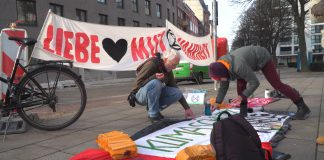 Zwei Menschen bemalen einen Banner vor dem Siemens-Gebäude in Hamburg.