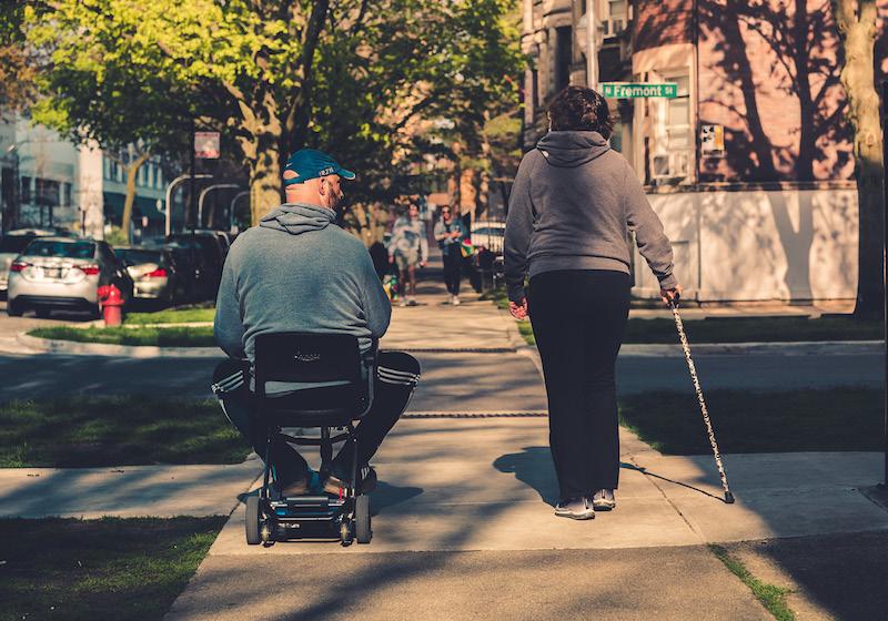 Ein Mann im Rollstuhl und eine Frau mit Gehstock beim Spazieren