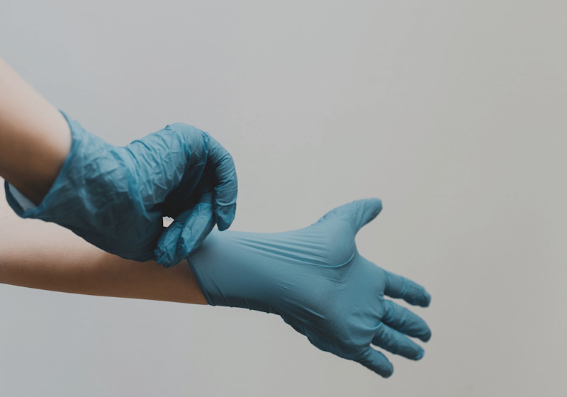 Zwei Hände in blauen Gummihandschuhen