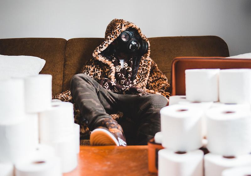 Ein Mann mit Atemmaske sitzt auf einer Couch umringt von Toilettenpapier