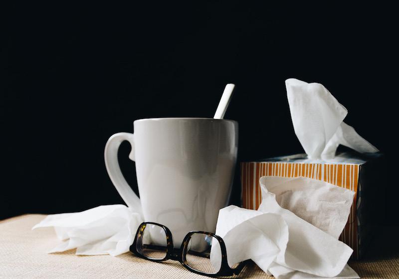 Auf einem Tisch stehen eine Teetasse und eine Box mit Taschentüchern