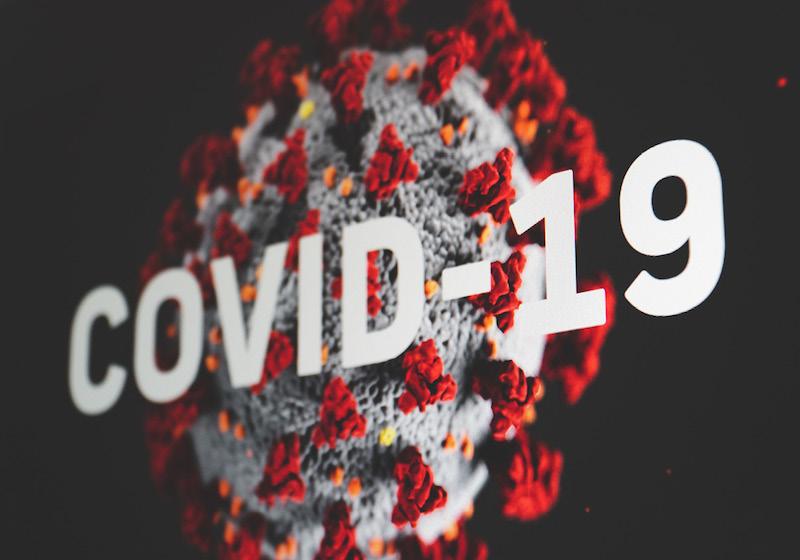 Weißer COVID-19-Schriftzug über Abbild einer Viruszelle