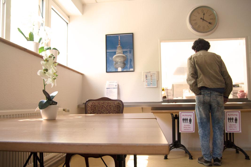 Ein Mann steht am großen Küchenfenster, um sich sein Essen zu holen.