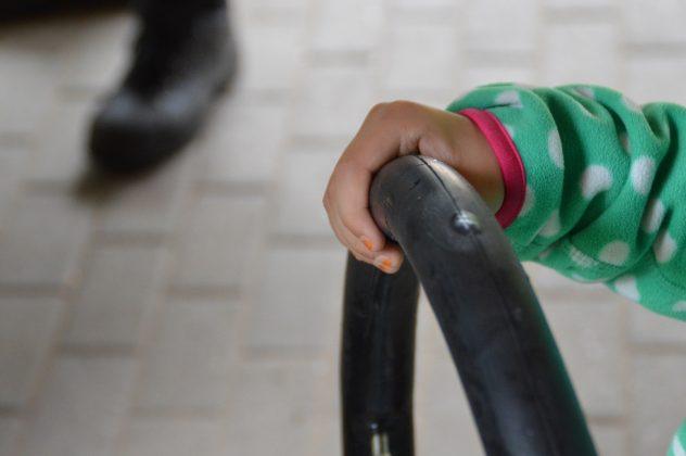 Eine Kinderhand hält einen geflickten Fahrradreifen