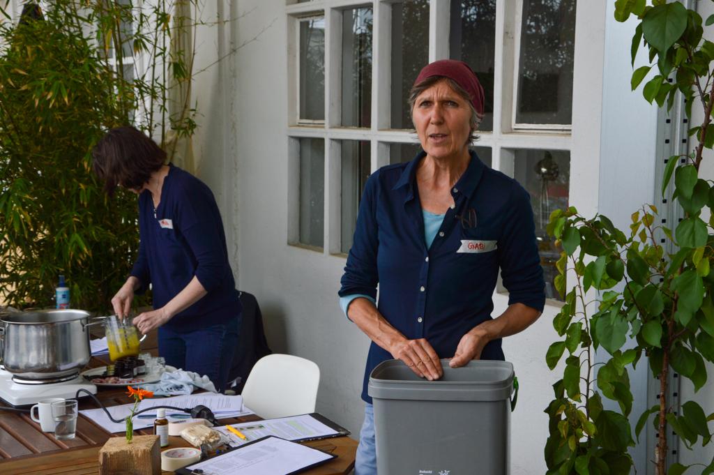 Während Barbara die Salbe mischt, erklärt Gabi das Konzept des Bokashi-Küchenkomposter. Foto: Maja Andresen