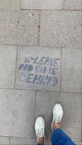 """""""Leave no one behin"""" ist in schwarzen Buchstaben auf den Boden gesprüht."""