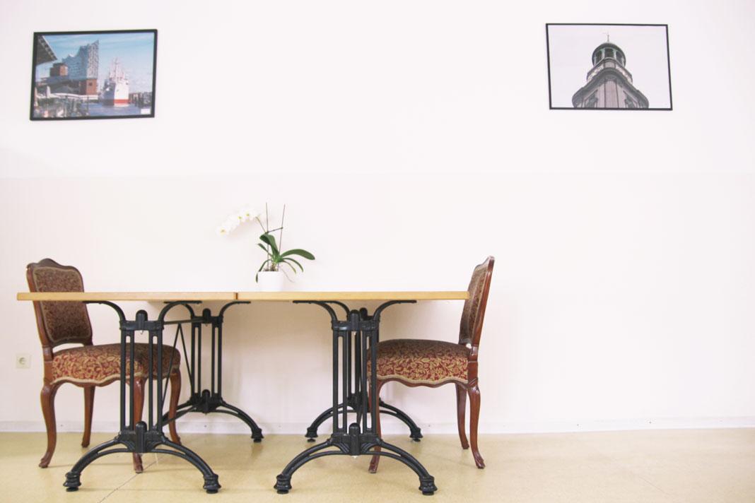 Eine einsame Plastik-Orchidee steht auf einer nackten Tischplatte.