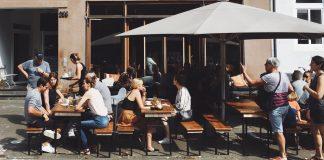Menschen auf Bänken vor einer Bar/Restaurant