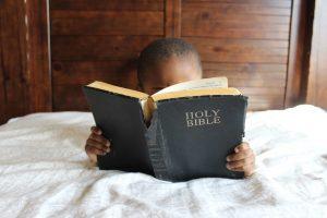Junge im Bett mit Bibel