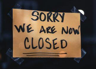 """Ein Schild mit der Aufschrift: """"Sorry, we are now closed"""" klebt an einer Scheibe."""