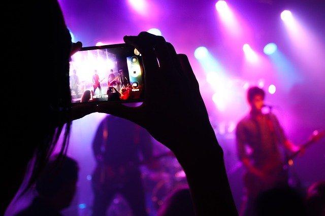 Person filmt Band mit Handy auf Konzert