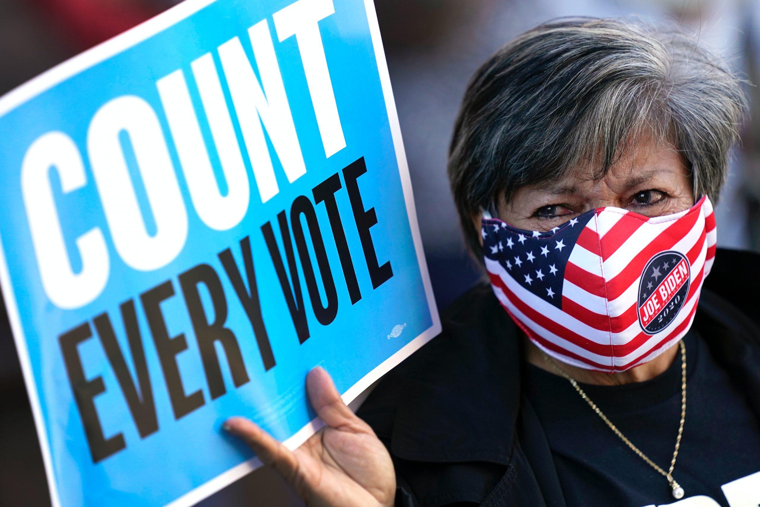 Eine Frau hält ein Schild mit dem Titel: Count every vote. Trumps Siegeserklärung erntet Kritik.