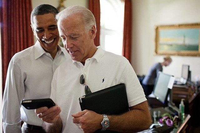 Barack Obama und Joe Biden schauen auf ein Smartphone