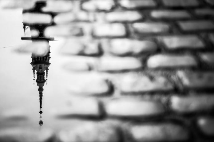 Kopfsteinpflaster-mit-Regenpfütze-Spiegelung-des-Michels