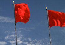 Die USA und der Sozialismus: Drei rote Fahnen vor blauem Himmel
