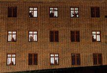 Ein Gefängnis von aßen. Hinter den vergitterten Fenstern Schatten von Insassen.
