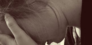 Thema: Corona in Frauenhäusern. Eine Frau stützt ihr Gesicht in ihre Hände.