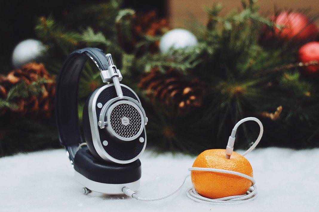 Ein Kopfhörer steckt in einer Orange und steht symbolisch für Weihnachtslieder