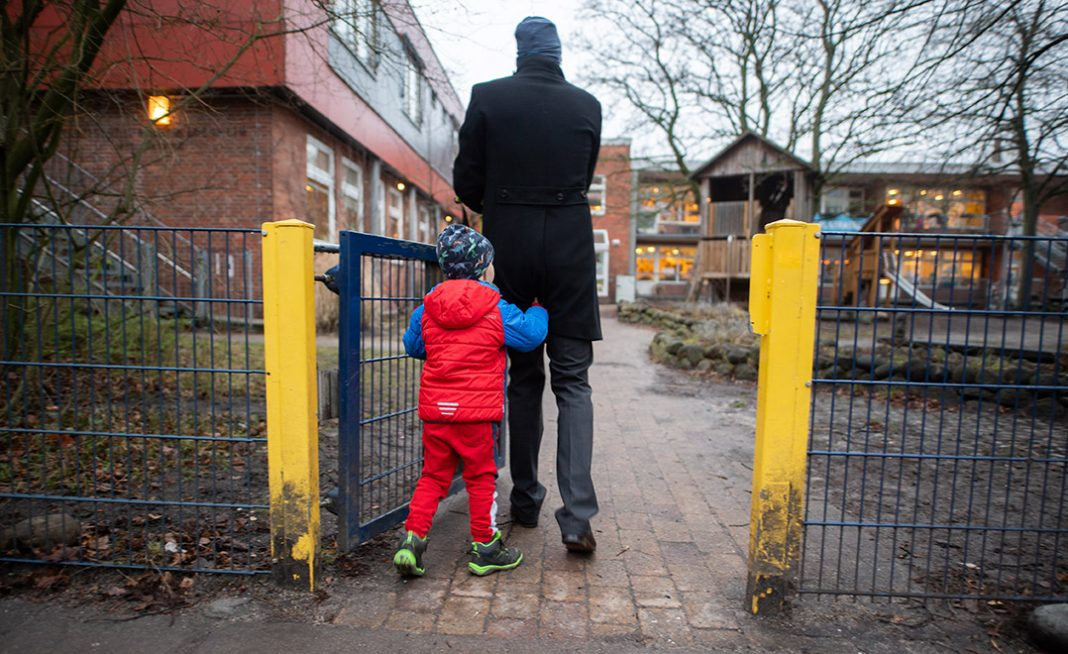 Ein Vater begleitet sein Kind auf das Gelände einer Kita.