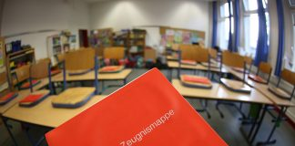 Eine Zeugnismappe ist in einem leeren Klassenraum einer Grundschule zu sehen.