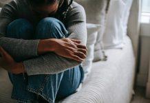 Frau sitzt auf Bett. Arme um Körper geschlungen