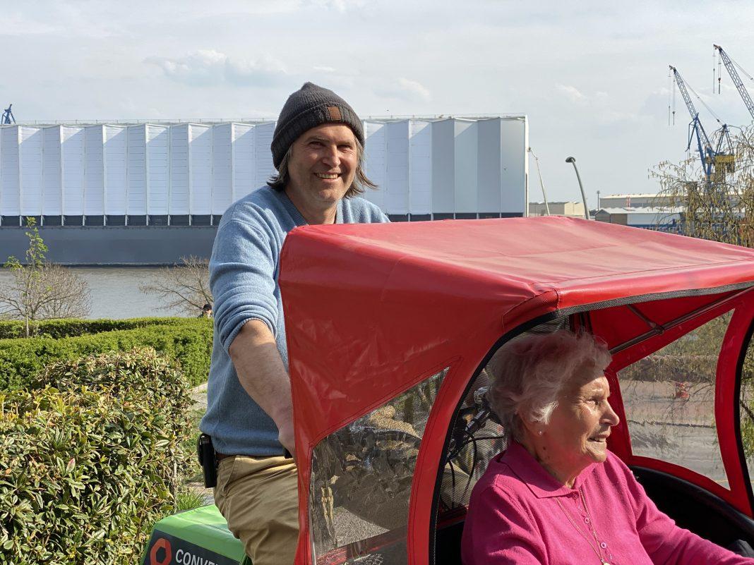 Marko Schier fährt die 93-Jährige Marta Bartsch in einer Rikscha am Hamburger Hafen