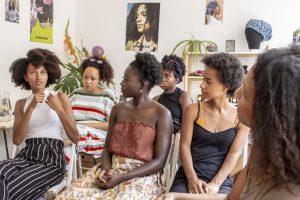 Sechs Frauen mit Afrohaaren, die an einem Haarworkshop von Abina teilnehmen. Sie sitzen in zwei Reihen. Eine Teilnehmerin spricht, die Köpfe der anderen sind ihr zugewandt.