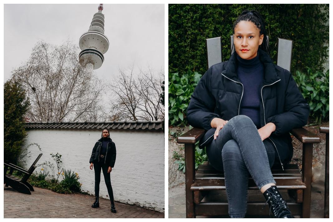 Black Power Germany Aktivistin Charlotte Nzimiro steht vor einer weißen Mauer in Planten un Blomen. Im Hintergrund ist ein Nadelbaum zu sehen.