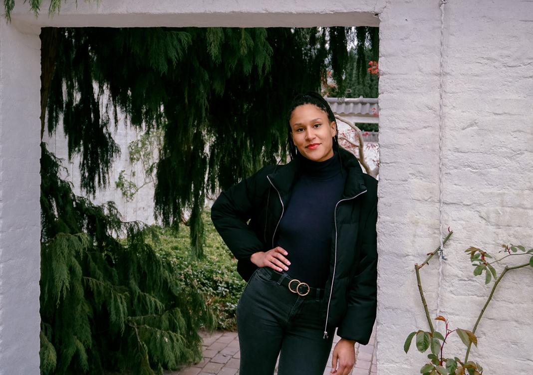 Black Power Germany Aktivistin Charlotte Nzimiro lehnt in Planten un Blomen an einer weißen Mauer. Im Hintergrund ist ein Nadelbaum zu sehen.