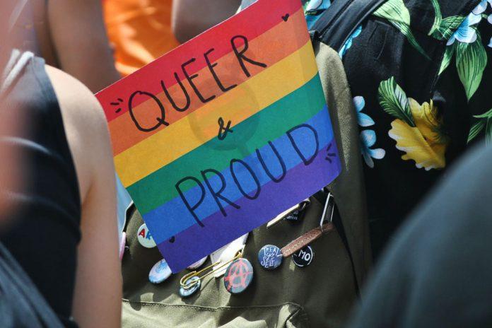Regenbogenflagge, auf der Queer & Proud steht in einem Rucksack.